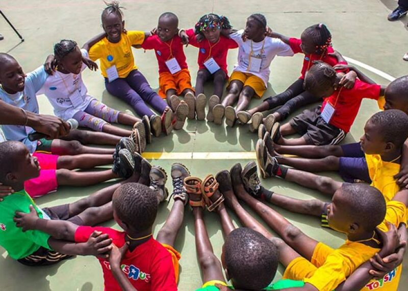 young athletes sitting in a circle with their feet together forming another circle.