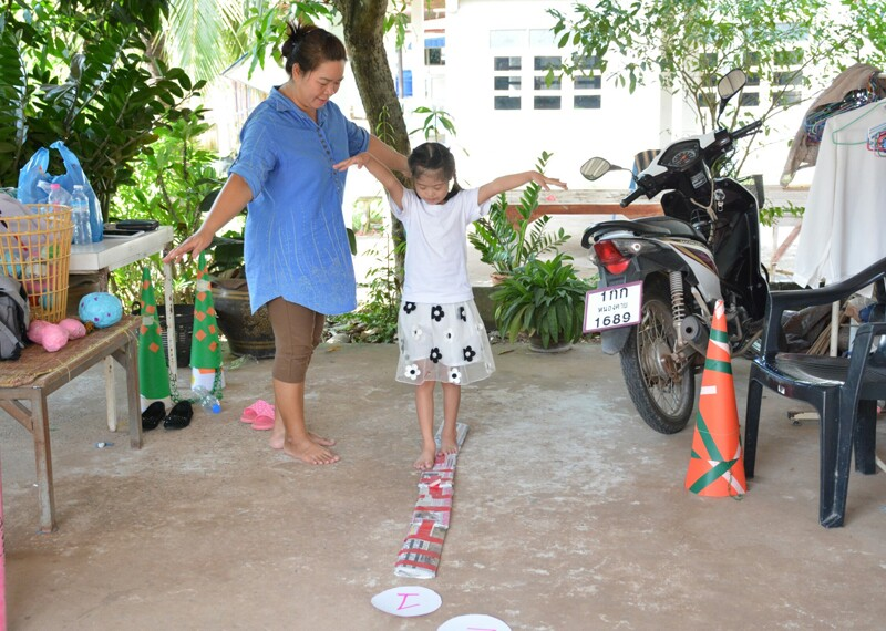 Young girl practicing balancing while older woman helps.