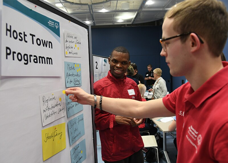 Special Olympics Deutschland Athlete forum, Nyasha standing next to a white board and an athlete standing in front of the white board putting stickers on note cards.