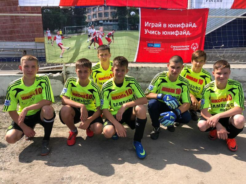 Seven boys in luminous yellow football jerseys, black shorts and football boots kneel in front of a banner branded by Special Olympics and Stavros Niarchos Foundation.