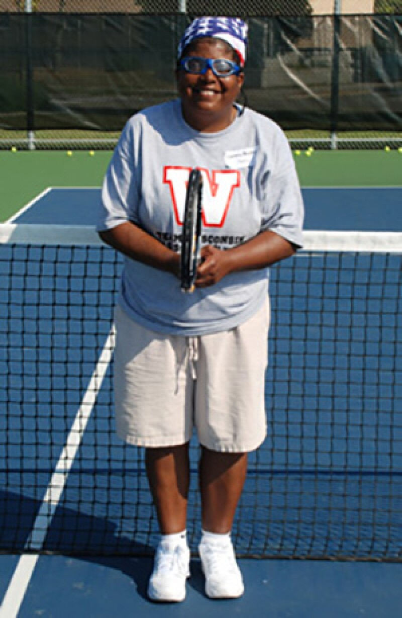 Cindy Bentley on the tennis court holding a racket in front of the net.