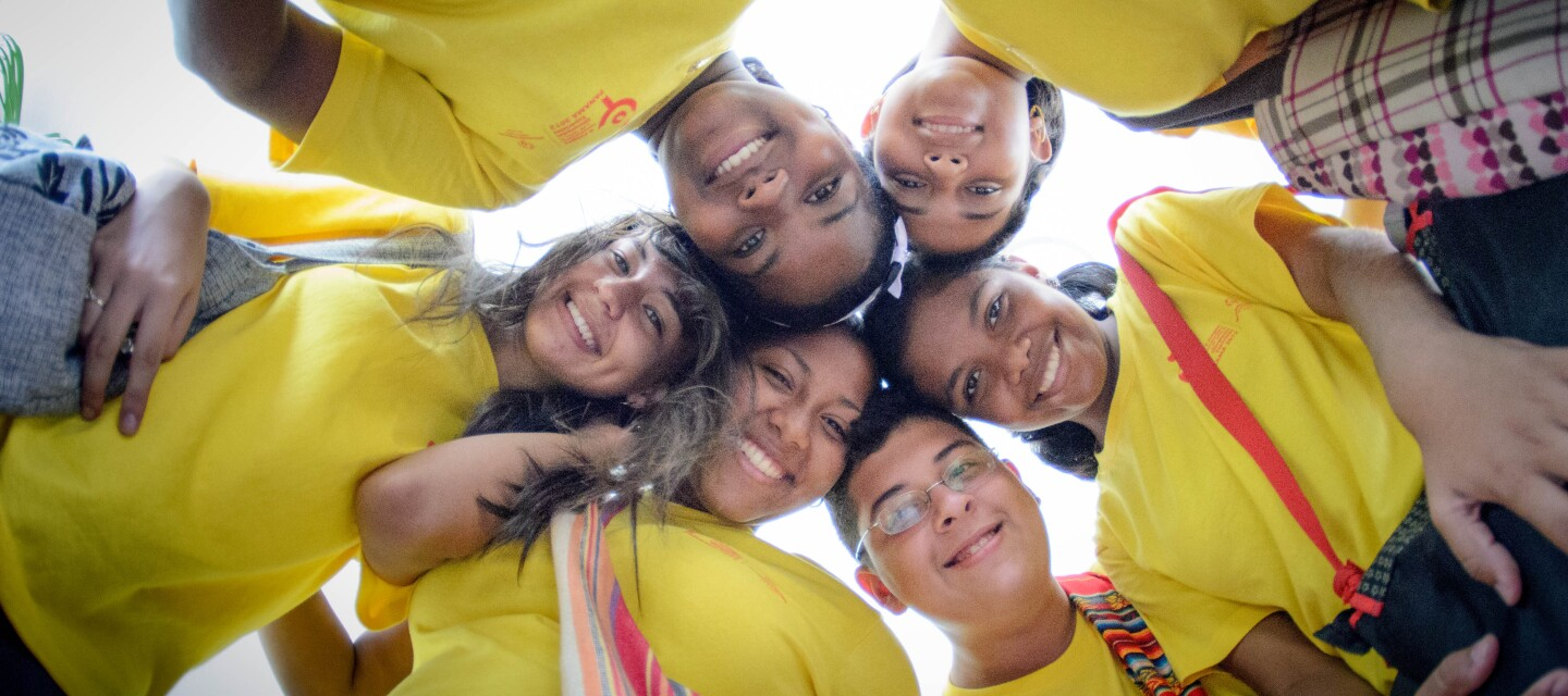 Children wearing yellow t-shirts standing in a circle smiling as they look down at the camera