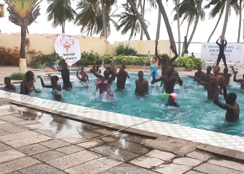 Two instructors are outside of the pool jumping and a group of athletes are inside of the pool jumping, training with resistance.