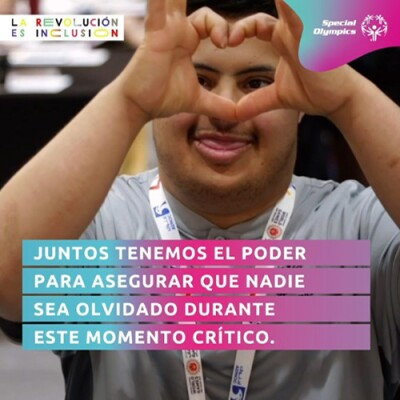"A Special Olympics athlete who got free health screenings in the Healthy Athletes Program during World Games Abu Dhabi 2019 makes a heart-shaped sign with his hands while looking at camera. Spanish text in front of him reads ""Together, we have the power to make sure nobody is left behind during this critical moment."""