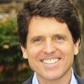 Mark Shriver smiling for a professional photo. He's outside in front of greenery.