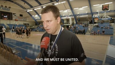 """Adult man in a black Play Unified shirt is speaking to an interviewer, text at the bottom reads, """"...and we must be unified."""""""