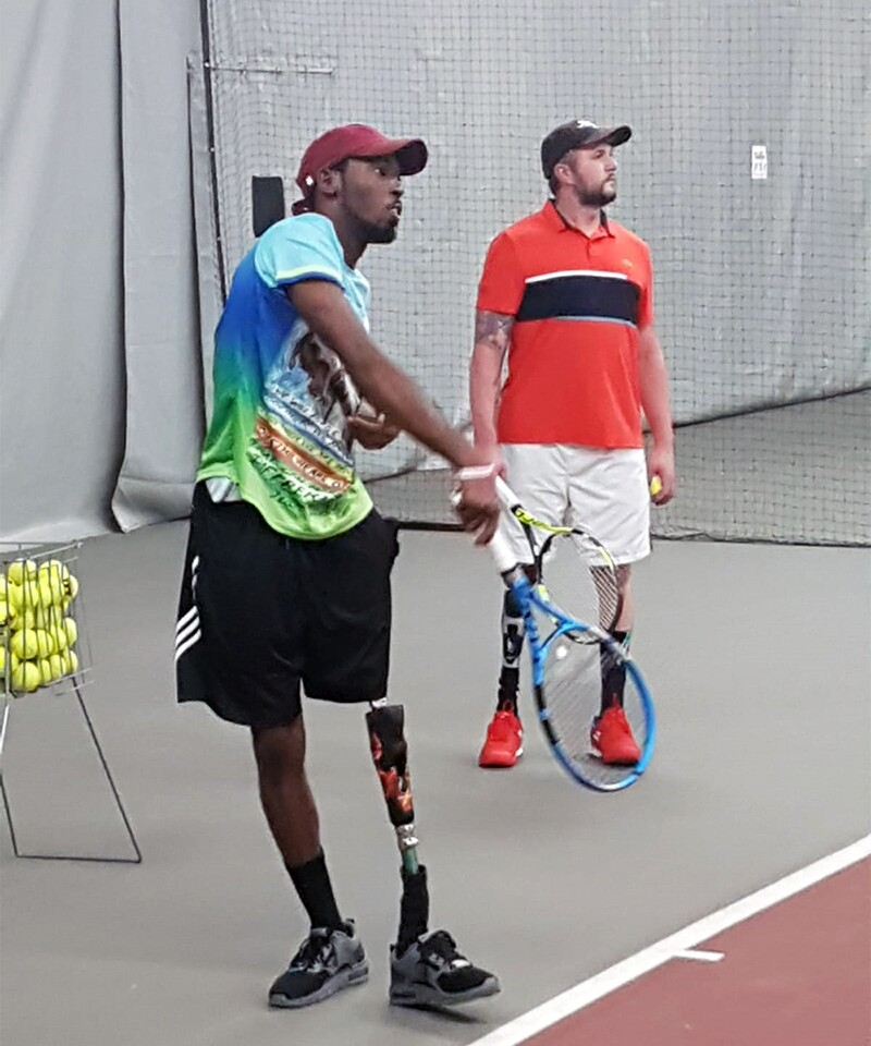 Dionte Fosters plays tennis with his new prosthetic leg; he just took a swing at a ball. Jeff Bourns is in the background watching while holding his racket and ball.