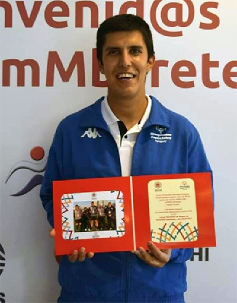 """Hassam stands in front of a step and repeat that says """"Secretaria Nacional de Deportes."""" He is holding a microphone."""