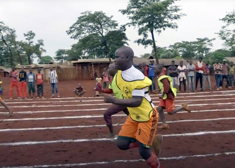 Malachie and four other athletes running a racing on a straight track while spectators watch.