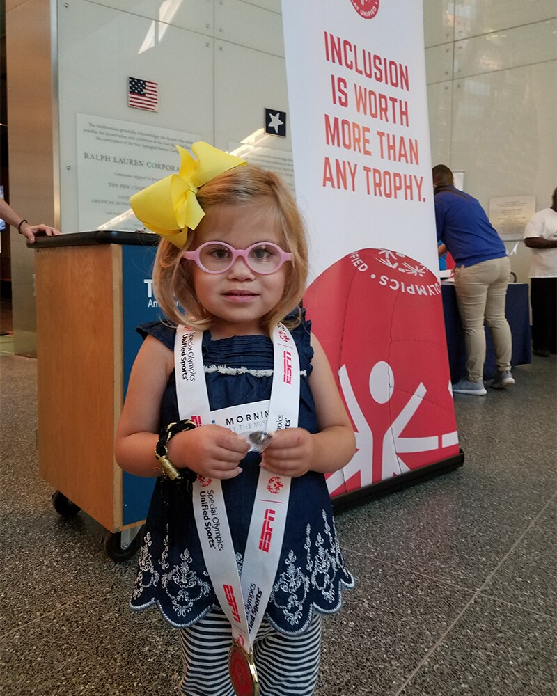 A young girl wearing pink glasses and a blue dress with white and blue horizontal striped leggings tries out a Special Olympics medal at the museum's hands-on section. She is standing in front of a Special Olympics sign banner that reads, Inclusion is worth more than a trophy.