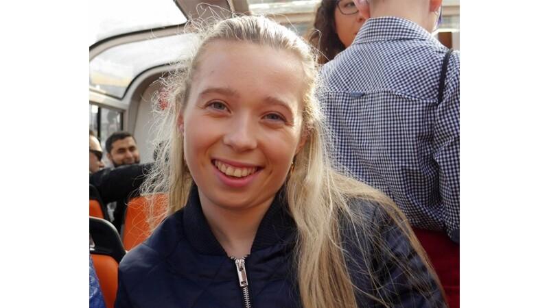 Kiera Byland smiling. Sitting on public transportation, long blond hair and blue eyes.