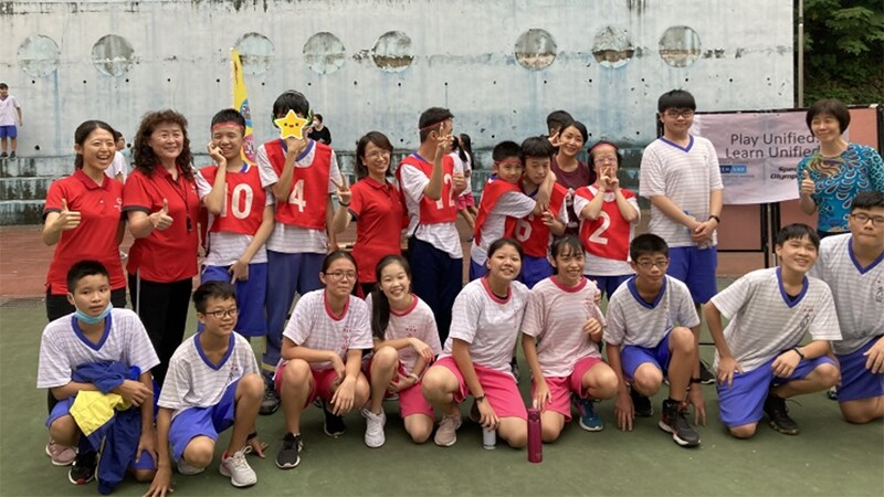 A group of around 20 students and teachers stands and crouches together. Everyone is smiling, some give thumbs up. The boys wear blue uniforms and the girls wear pink uniforms.