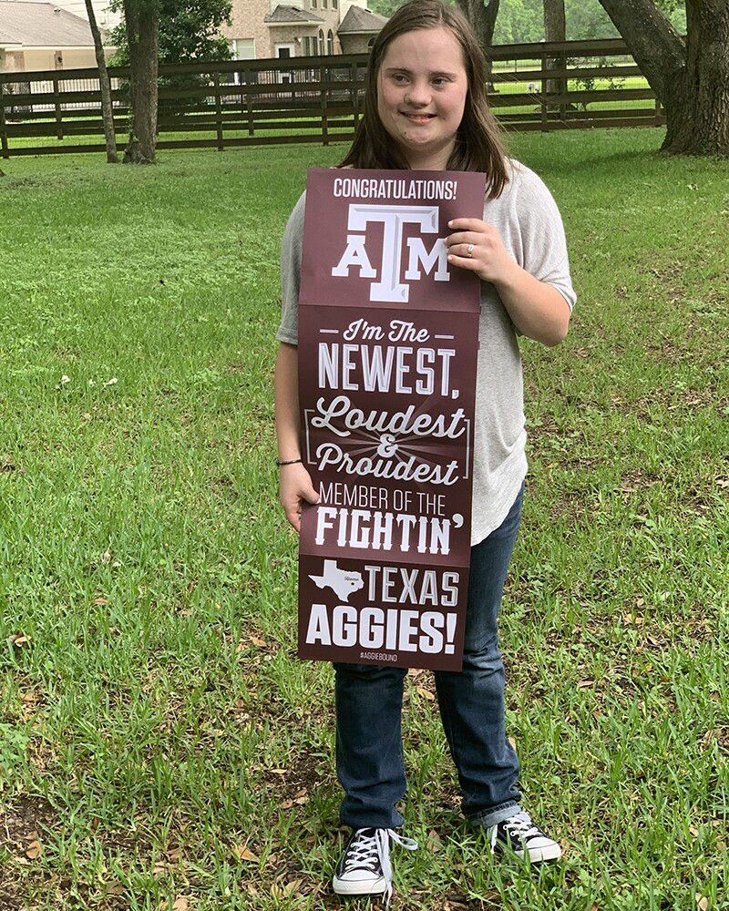Girl standing in the grass holding a sign that reads: Congratulations! ATM i'm the newest loudest and proudest member of the fightin texas aggies!