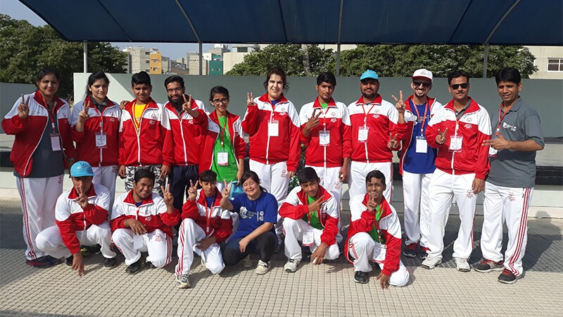 Jasmine poses with athletes from Special Olympics Pakistan. They are wearing matching tracksuits, and many of them are doing peace signs with their hands.