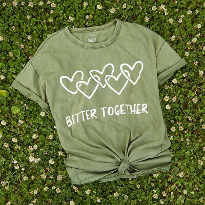 """Aerie """"Better Together"""" green t-shirt on a bed of dandelions."""