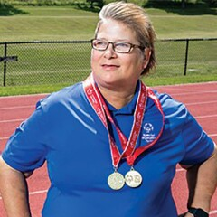 Maryann Gonzales standing in front of a track and field with awards draped around her neck.