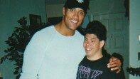 """Dwayne """"The Rock"""" Johnson standing next to Milton with his arm around his shoulder."""