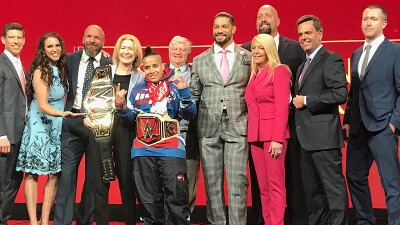 Representatives from Special Olympics and WWE stand for a group photo; Special Olympics New York Athlete Angel (power lifter) stands in the center with a champion ship belt around her waist.