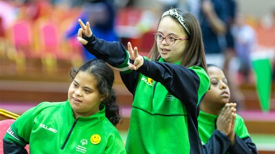 Three female athletes from the Special Olympics Saudi Arabia team, the young girl in the middle is giving the peace sign with both hands.