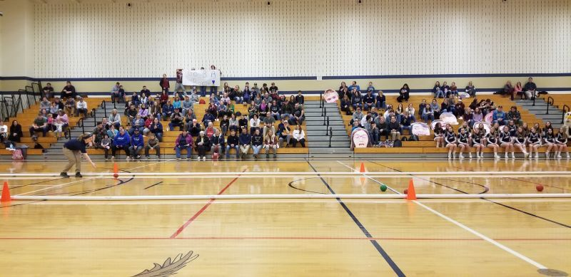 A gymnasium full of high school students cheers for a Special Olympics Unified bocce team during competition.