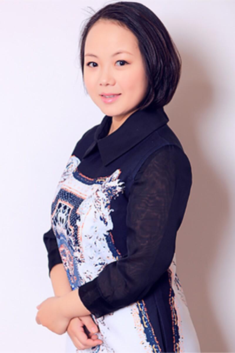 A professional portrait of Principal Liu Sha, standing against a wall.