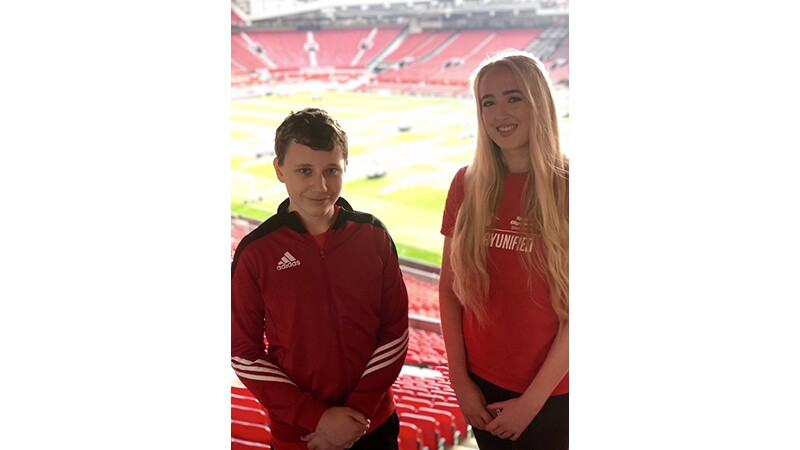 Joel and Olivia, Unified Partners from Special Olympics Great Britain standing in the stadium seating area posing for a photo together. Olivia has on a play unified t-shirt.