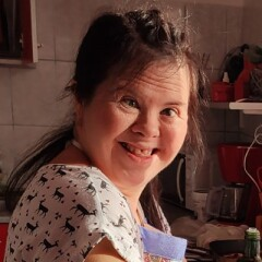 Raluca Ioana Avram smiling while she is in the kitchen preparing a dish.