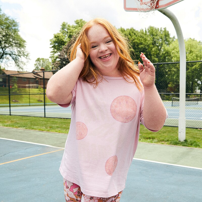 Emma smiles and poses on a basketball court with her hand in her hair wearing a t-shirt and leggings.