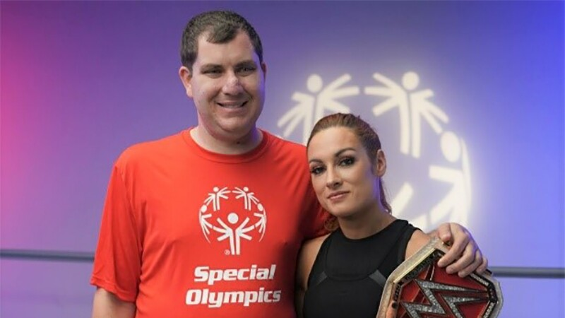 """Greg standing next to Becky Lunch in the """"Squared Circle"""" for the WWE and School of Strength workout."""