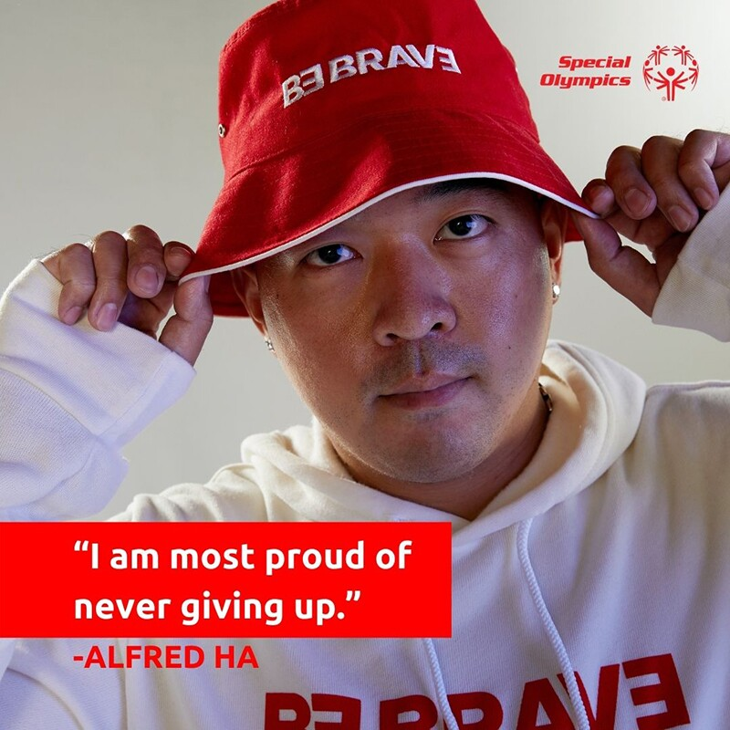 """Alred Ha in a red had and white be brave hoodie. Text reads: """"I am most proud of never giving up."""" - Alfred Ha"""
