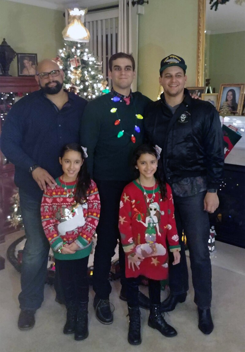 Coach Roberto's three sons and and two granddaughters standing in front of a Christmas Tree.