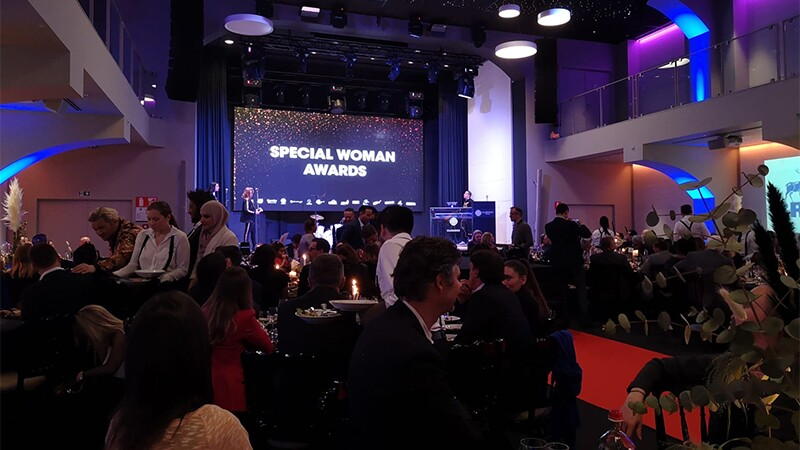 Special Woman Awards illuminated on a projection screen in the front of a hall with people sitting in the foreground.