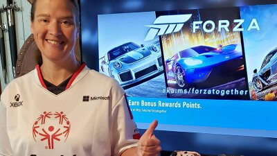 Woman poses with a thumbs up in front of gaming console.