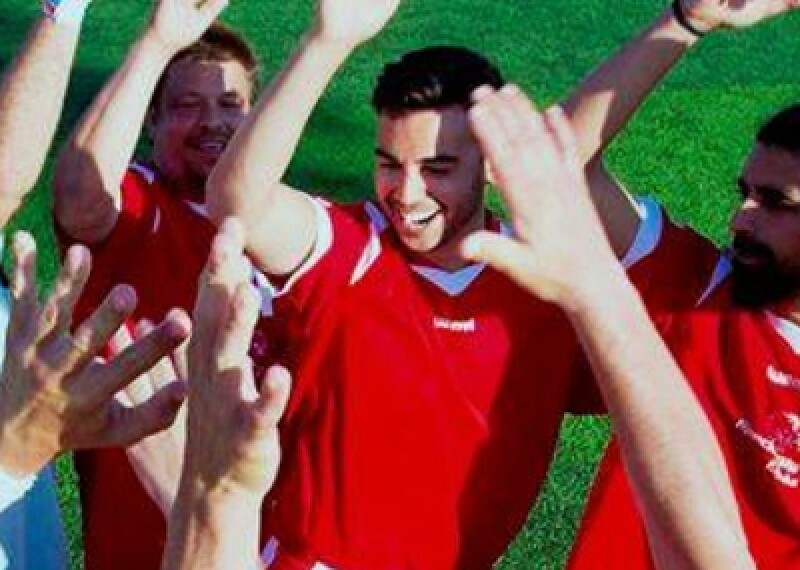 Players on a field celebrating and giving one another high-5s.