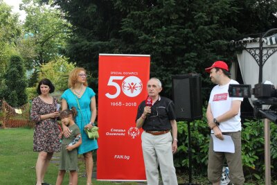 Two women, one girl and two men stand in front of a Special Olympics banner in a garden setting. The man is holding a red microphone.