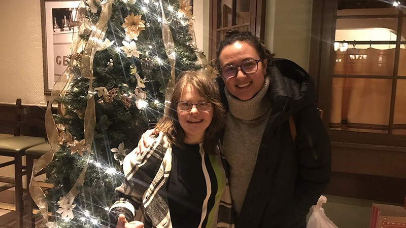 Hanna Atkinson and Stephanie Levine standing in front of a Christmas tree.