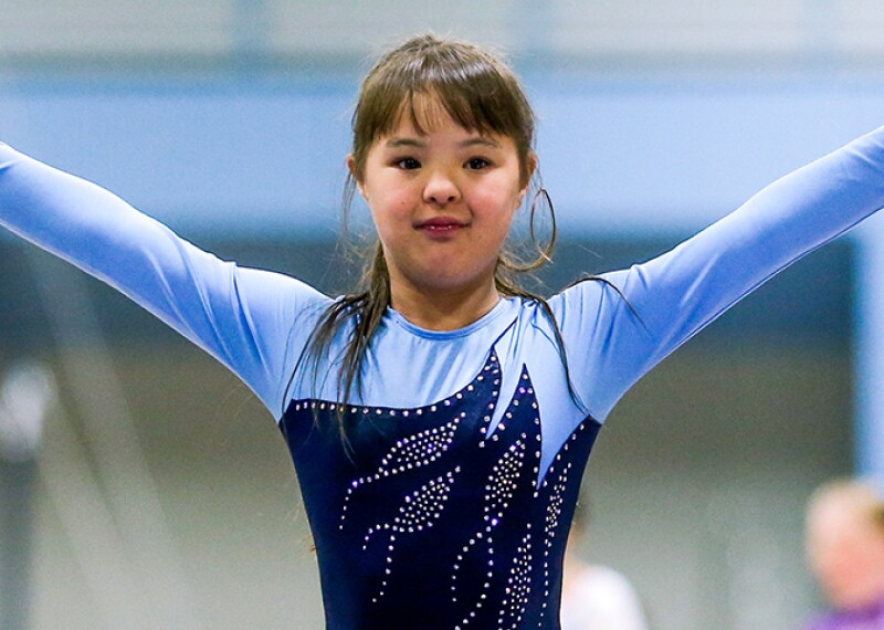 Young girl in a blue leotard raising her arms as she finishes her routine.