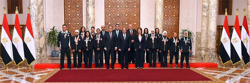 The Egyptian Unified Football team and the president of Egypt lined up in front of a wall with 3 Egyptian flags on each side.