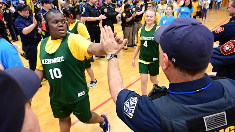 Athletes and police officers give one another high-5s while walking down a line next to one another.