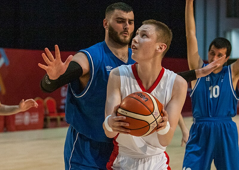Two teams on the court and competing in basketball. Young man is going for a shot and a player from the opposing team is trying to block him.