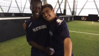 Gerald standing next to a young man on an indoor field and hugging one another.