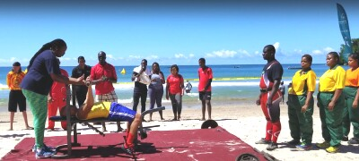 Athletes power lifting on the beach in Trinidad. One male athlete is lifting and a female is spotting him. other athletes are lined up waiting for a turn. Waves are crashing in the background and it's bright and sunny out.