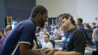 A volunteer holding athletes hands and giving him words of encouragement and smiling at one another.