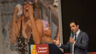 "David Evangelista speaking behind a podium that reads, ""inclusion in Motion."""