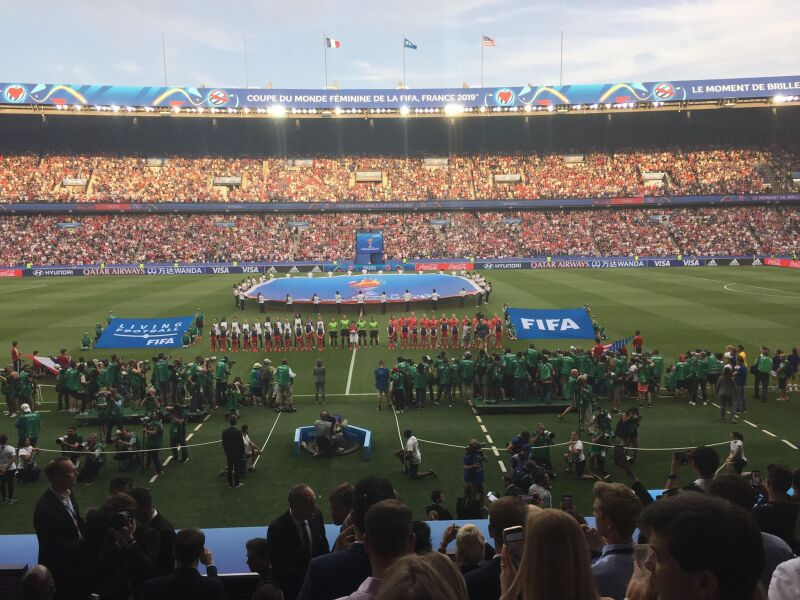 View of a football pitch in a crowded stadium with teams lined up on the football pitch. A FIFA flag and a large flag of the FIFA logo are being held up by people on the football pitch.