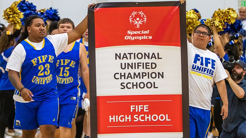 Two students holding up the National Unified Champion School banner for Fife High School with the student body standing behind them.