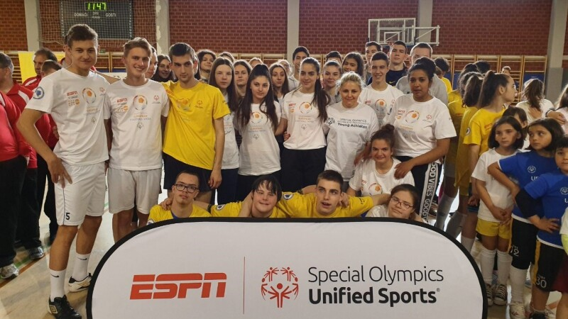 A group of young people in yellow and white t-shirts stand behind an 'ESPN and Special Olympics Unified Sports' banner facing the camera on an indoor court.