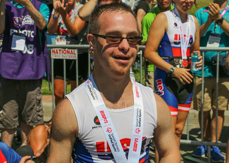 Ben from team US standing in front of other athletes, spectators, and fans smiling for a photo op.