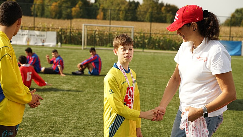 A young man in a yellow football jersey shakes hands with a woman in a white t-shirt and red baseball cap. They are standing on a football pitch and there are other footballers in the background.