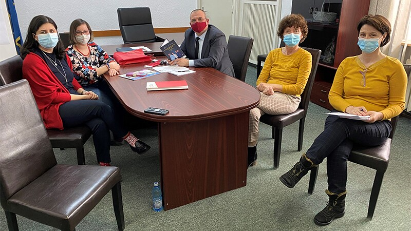 Five people wearing masks sitting around a table while respecting social distancing.